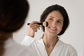 Happy young woman look in mirror doing makeup
