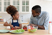 Pleasant african father talking with preteen daughter while cooking breakfast
