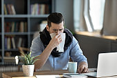 Unhealthy ill stressed young 30s businessman having first flu symptoms.