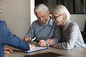 Excited older couple clients close deal at meeting