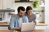 Happy couple using laptop in kitchen, making internet payment