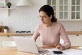 Focused millennial woman in eyeglasses paying bills online.
