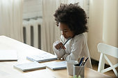 Thoughtful focused African American little girl studying at home