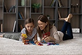 Happy young mother and teen daughter play at home