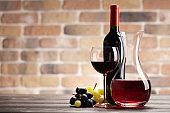 Wine decanter, bottle, glass of red wine and grapes