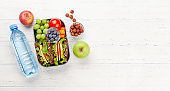 Healthy school lunch box with sandwich and fresh vegetables