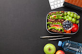 Healthy office lunch box with sandwich and fresh vegetables