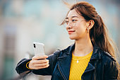 Portrait of confident Asian businesswoman with smart phone in city.