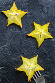 fresh carambola star fruit cut into slices ready to cook and eat on the table for healthy meal snack outdoor top view copy space for text food background rustic image keto or paleo diet