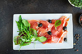 Dry jamon Italian Prosciutto Serrano, Bellota, Crudo or Parma ham portion on the table healthy meal top view copy space for text food background rustic image