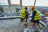 Two workers in protective clothing and safety helmets installing plastic pipes using soldering iron on balcony of flat of building under construction