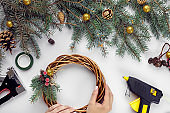 Top view of female hands make a Christmas wreath. Packed gifts and scrolls, spruce branches and tools on white table