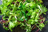 Healthy salad, leaves mix salad mix micro greens, juicy snack ready to cook and eat on the table for healthy meal snack outdoor top view copy space for text food background rustic image keto or paleo