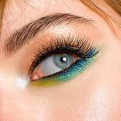 Face of an young girl close-up with a green color makeup. Stylish makeup.