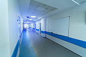 Long hospital hall in light white and blue colors. Many doors and whiteboard on wall.