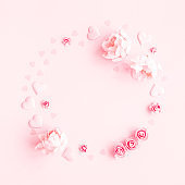 Valentine's Day background. Wreath made of pink flowers, hearts on pastel pink background. Valentines day concept. Flat lay, top view, copy space