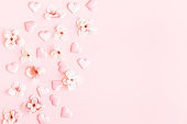 Valentine's Day background. Pink flowers, hearts on pastel pink background. Valentines day concept. Flat lay, top view, copy space
