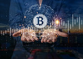 Businessman is holding a bitcoin as part of a business network, Cryptocurrency blockchain connection, Technology and financial investment background concept.