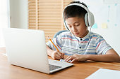 Asian little boy video call online via the internet tutor on a computer laptop with headphone. Asia man doing homework. Concept online learning at home