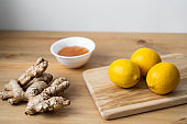 A white cup of green natural tea with ginger, lemon and honey on wooden rustic background.