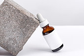Close-up serum essence in glass bottle on stand background. Isolated skincare oil