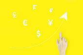Global currency exchange concept. Young woman's hand pointing finger with hologram world currencies and arrow up on yellow background. Successful international financial investment concept