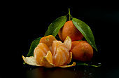 Fresh and ripe tangerines, pieces, green leaves and cross section on black background.
