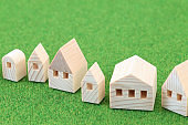Wooden toy house on green background
