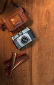 Still life flat lay retro camera with film negative on wooden background