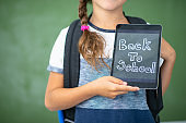 Elementary female student holding back to school sign