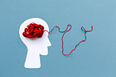 World Alzheimer's day. Paper silhouette of human head with red tangled threads on blue background. Flat lay. Concept of mental health and dementia