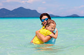 Mother and kid at tropical beach. Family vacation.