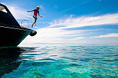 Child jumping into sea water. Yacht vacation.