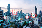 Hologram of Padlock on sunset panoramic cityscape of Bangkok, Asia. The concept of cyber security intelligence. Multi exposure.