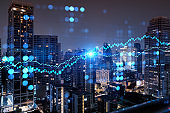 FOREX graph hologram, aerial night panoramic cityscape of Bangkok, the developed location for stock market researchers in Asia. The concept of fundamental analysis. Double exposure.