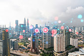 Abstract technology icons hologram over panorama city view of Kuala Lumpur, Malaysia, Asia. The concept of people networking and connections. Double exposure.