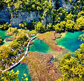 Aerial morning view of Plitvice National Park. Colorful spring scene of tourists walking on the bridge in green forest with lakes and waterfalls. Great countryside view of Croatia, Europe. Traveling concept background.