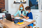 Mom and son do their homework, study online on the Internet. The concept of preschool education, home schooling of quarantined children during the coronavirus pandemic, covid-19