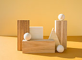 Geometrical figures composition. Three-dimensional wooden objects on yellow background. Balance, art and design concept.