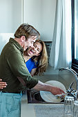 Man washing the dishes with his wife next to him.