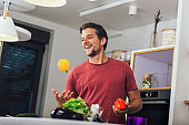 Caucasian young man throwing up vegetable in the kitchen.
