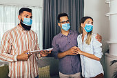 Couple in medical masks standing in the new house with male real-estate agent.