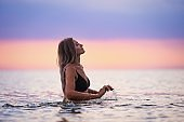 A girl with blond hair in a black swimsuit splashes to the sides while sitting in an estuary on a sunset background