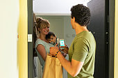 Mother with baby at the door paying for delivery with a card