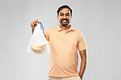 happy man holding reusable string bag with bananas