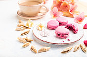 Purple macarons or macaroons cakes with cup of coffee on a white concrete background decorated with flowers. Side view, close up, selective focus.