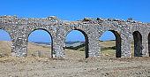 Roman aqueduct that runs in the middle of the field made with arches and with the right slope to bring water