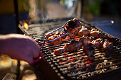 Chef cooking jerk barbecue BBQ chicken on the grill hand turning food