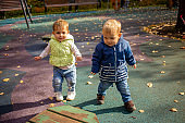 two cute toddlers boy and girl walk in the autumn park together. friendship since childhood concept