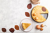 Autumn onion pie decorated with leaves and cup of coffee on gray concrete background. Top view, flat lay, copy space.